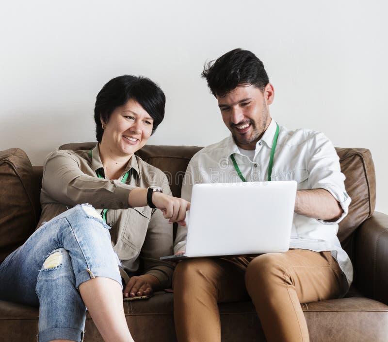 Verbinden Sie das Arbeiten an dem Laptop, der zusammen auf Couch sitzt stockfoto