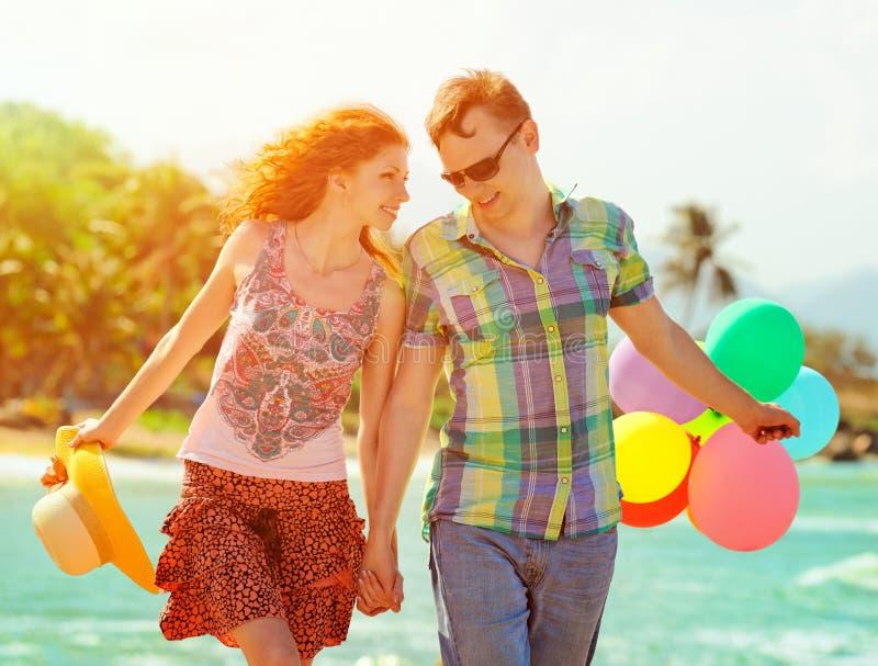 Verbinden Sie das Gehen auf den Strand mit Luft farbigen Bällen lizenzfreie stockfotografie