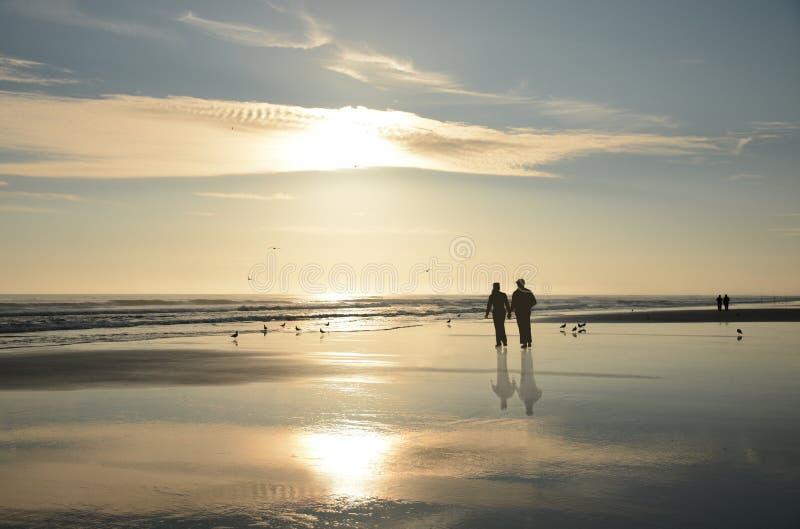Verbinden Sie das Gehen auf schönen nebeligen Strand bei Sonnenaufgang lizenzfreie stockbilder