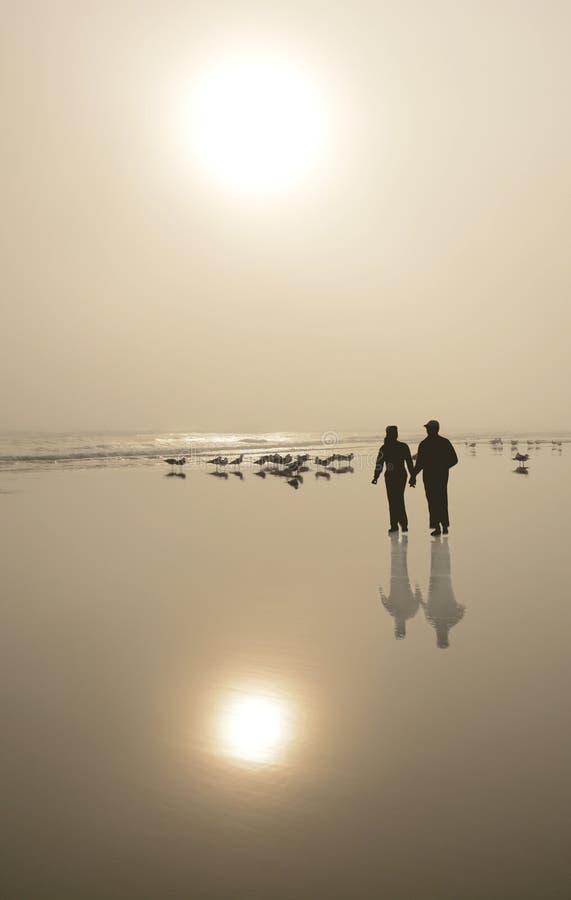 Verbinden Sie das Gehen auf schönen nebeligen Strand bei Sonnenaufgang stockfotografie
