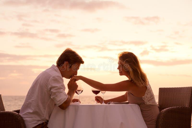 Verbinden Sie das Genießen romantischen sunnset Abendessens auf dem Strand stockbild