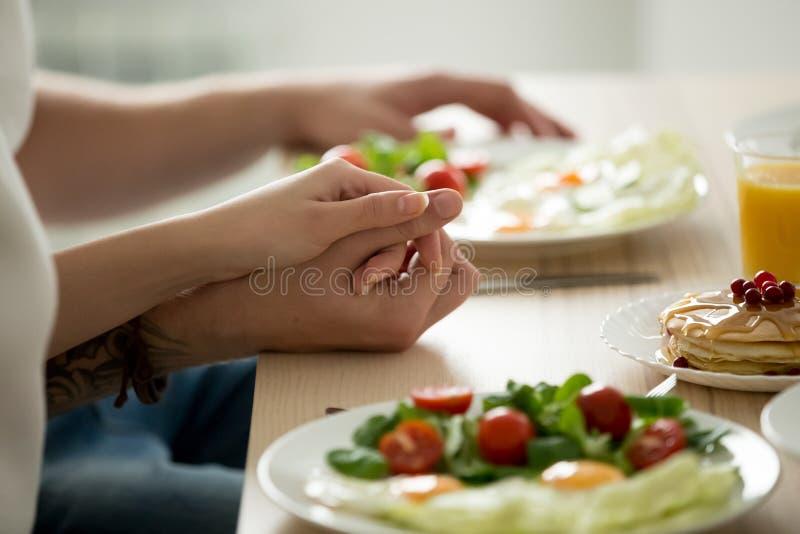 Verbinden Sie das Händchenhalten, das zusammen gesundes Frühstück, nah genießt lizenzfreies stockbild