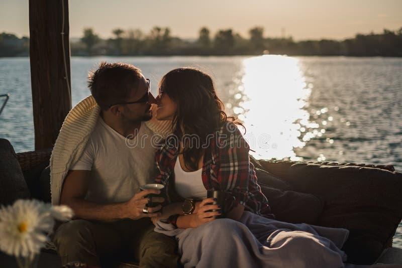 Verbinden Sie das Halten des Kaffees und das Küssen durch den Fluss im Sonnenuntergang stockbild