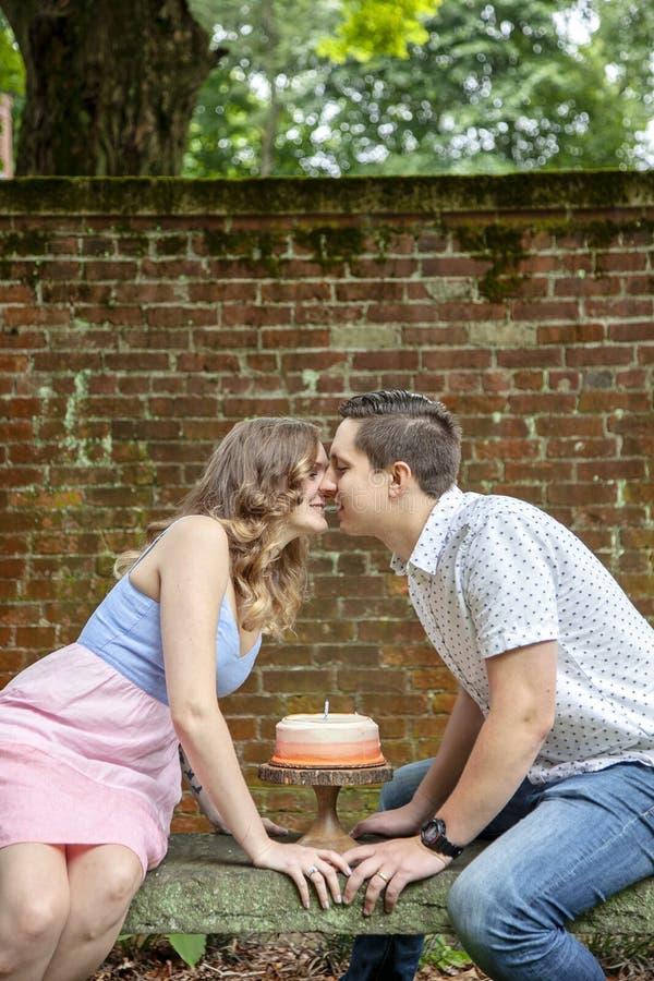 Verbinden Sie das Küssen über dem Kuchen, der einen Jahrjahrestag feiert stockfoto