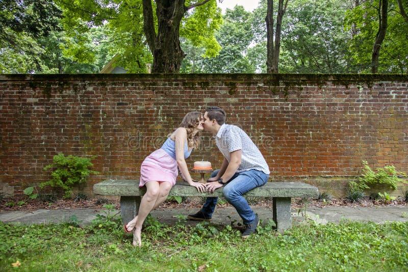 Verbinden Sie das Küssen über dem Kuchen, der einen Jahrjahrestag feiert stockbild