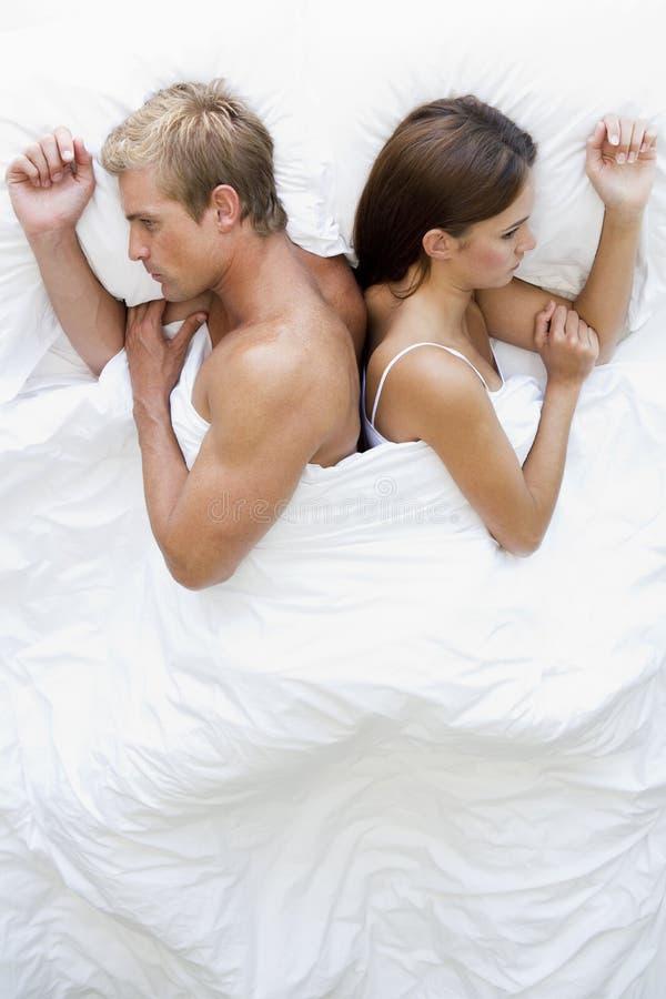 Verbinden Sie das Lügen im Bett zurück zu der Rückseite, die unglücklich schaut lizenzfreies stockbild