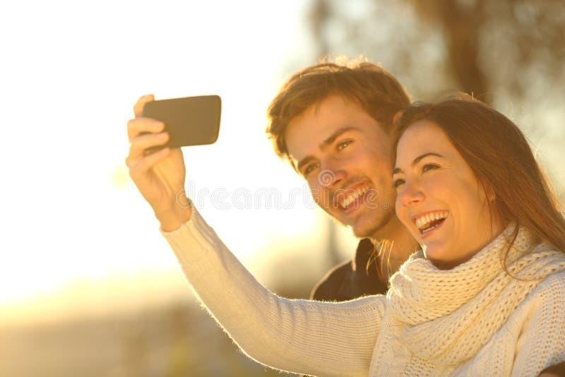 Verbinden Sie das Machen von selfie Foto mit einem intelligenten Telefon bei Sonnenuntergang stockfotos