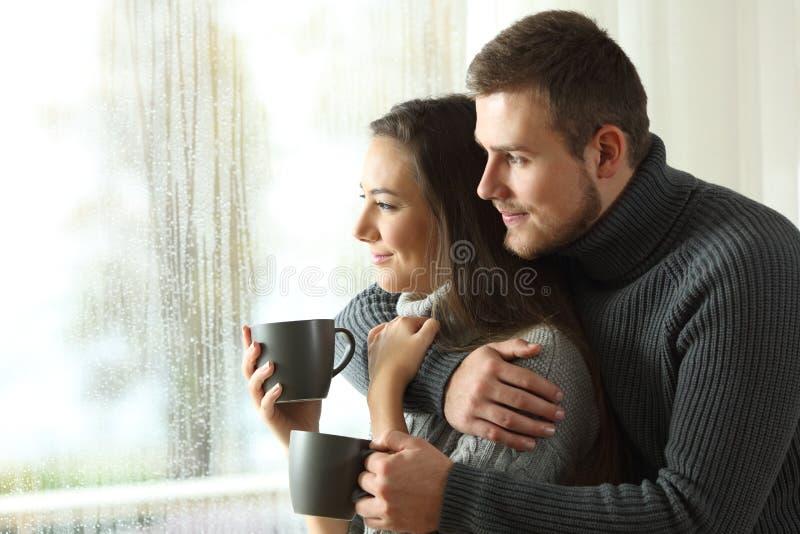Verbinden Sie das Schauen durch ein Fenster an einem regnerischen Tag lizenzfreie stockfotos