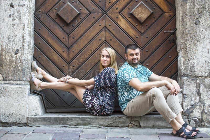 Verbinden Sie das Sitzen auf den Schritten des alten Hauses Porträt von liebevollen Paaren, junge Familie lizenzfreie stockfotos