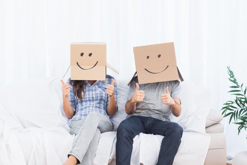 Verbinden Sie das Sitzen mit Pappschachteln auf dem Kopf, der Daumen aufgibt lizenzfreie stockbilder