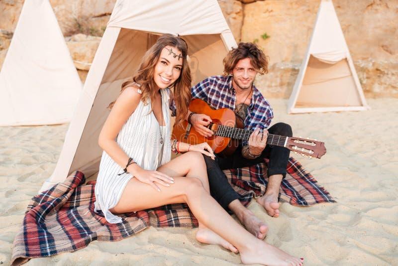 Verbinden Sie das Sitzen und das Spielen der Gitarre im Tipi auf dem Strand stockfotos