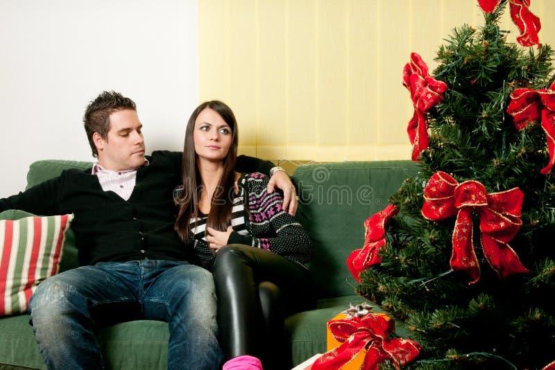 Verbinden Sie das Sitzen vor Weihnachtsbaum lizenzfreie stockfotografie
