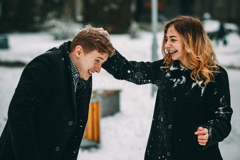 Verbinden Sie das Spielen mit dem Schnee und Freundin, die einen Ball in Winterurlaube werfen stockbild