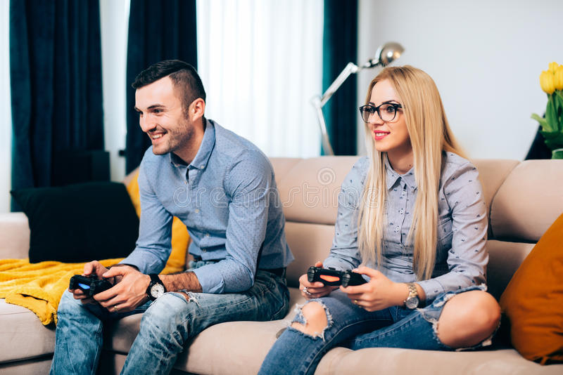 Verbinden Sie das Spielen von von Computerspielen und -Videospielen auf Konsole beim Sitzen auf Sofa am neuen Haus stockfoto