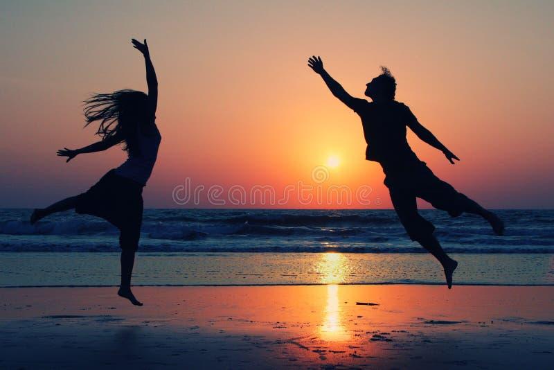 Verbinden Sie das Springen auf Hintergrund von See am Sonnenuntergang stockfotos