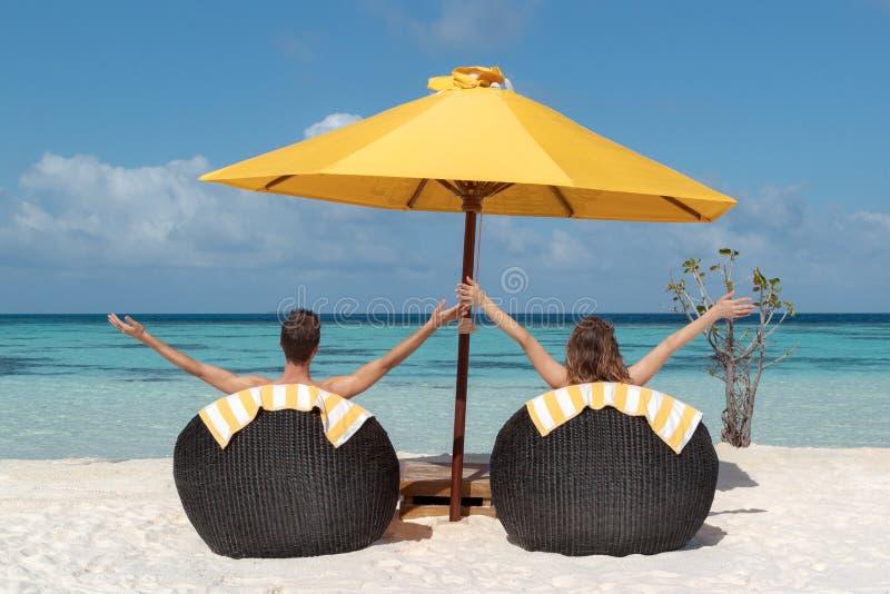 Verbinden Sie in den Flitterwochen, die auf Sonnenstühlen in den Malediven liegen Haarscharfes blaues Wasser als Hintergrund Arme lizenzfreie stockfotografie