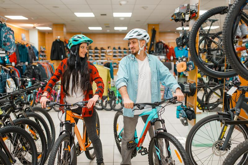 Verbinden Sie in den Sturzhelmen, die Fahrräder im Sportgeschäft wählen lizenzfreies stockfoto