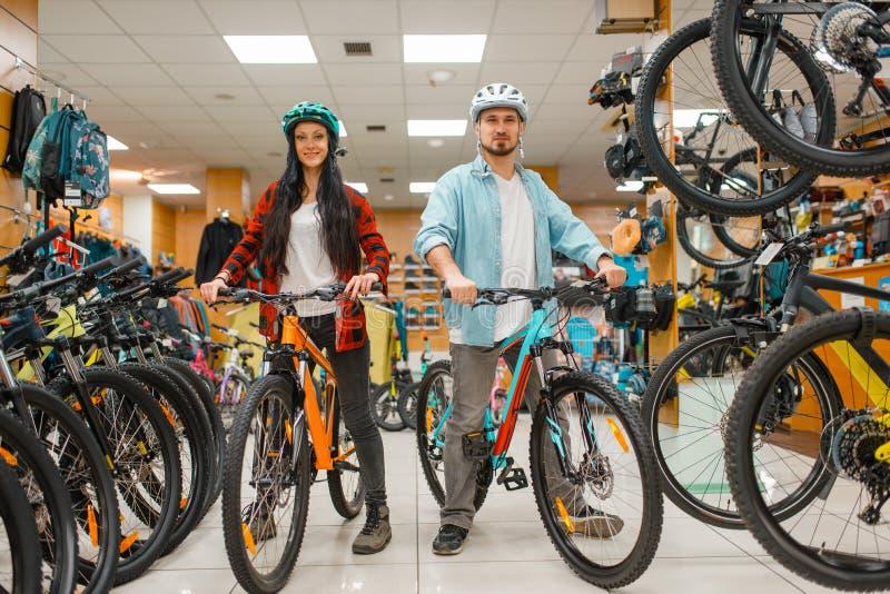 Verbinden Sie in den Sturzhelmen, die Fahrräder im Sportgeschäft wählen lizenzfreie stockbilder