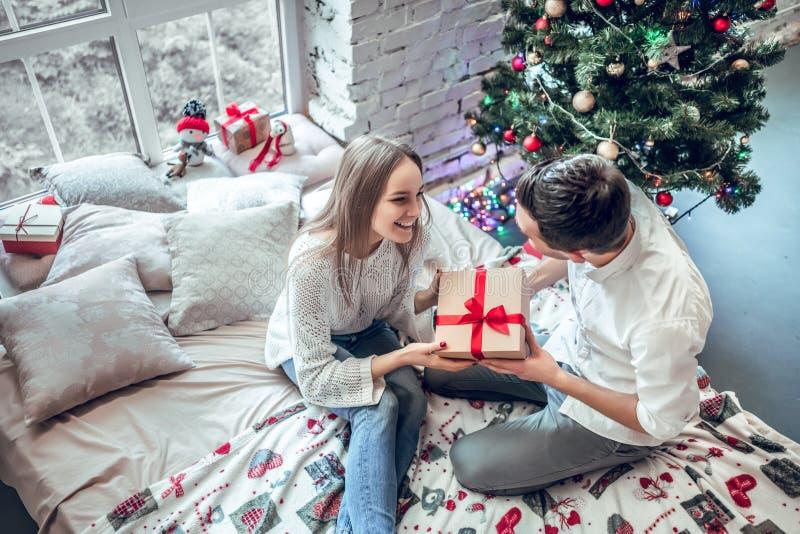 Verbinden Sie in der Liebe, die auf Bett nahe verziertem Weihnachtsbaum sitzt, Weihnachtsgeschenke austauscht und Spaß hat lizenzfreie stockfotos