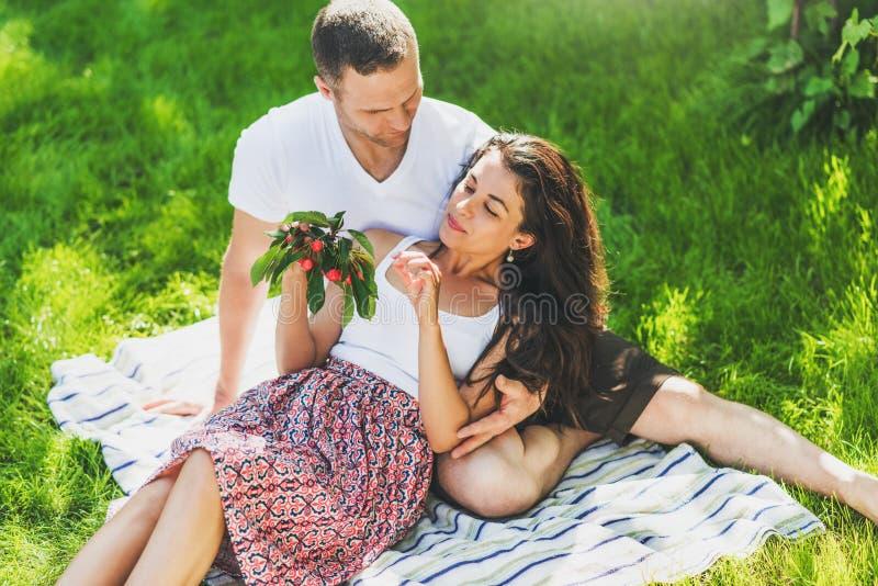Verbinden Sie in der Liebe, die auf einer im Freien gesunden Kirsche Essens der Picknickdecke sitzt Kaukasischer Mann und Frau, d stockbilder