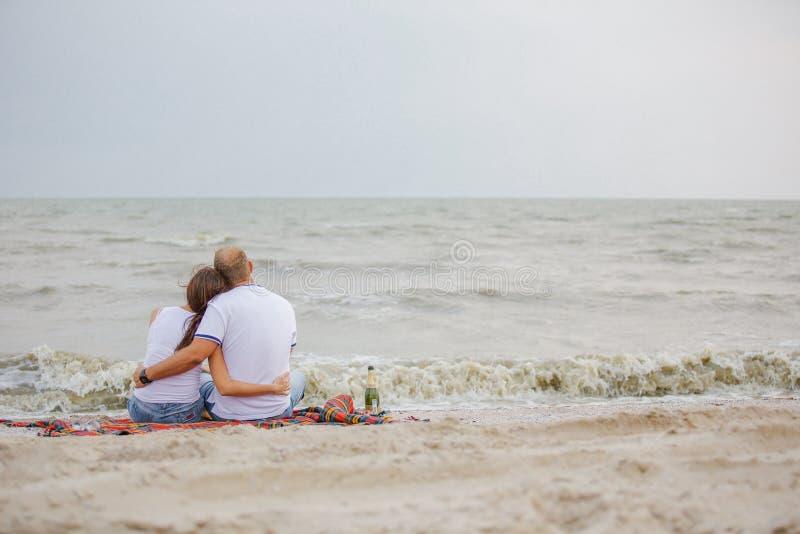 Verbinden Sie in der Liebe, die zurück auf dem Strand durch das Meer, die Flitterwochen sitzt, Romanze stockfotos