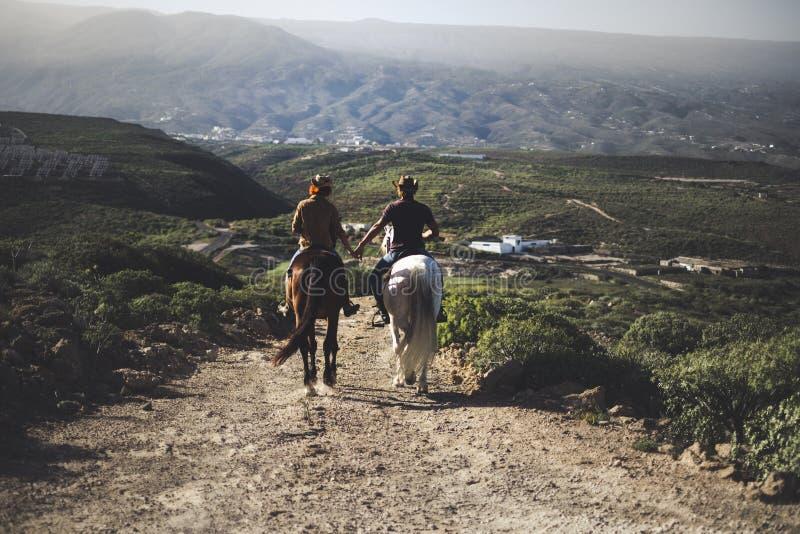 Verbinden Sie in der Liebe, die zwei schöne Pferde reitet, in einem Reiseabenteuer für alternativen Lebensstil und Ferien zusamme stockfotografie
