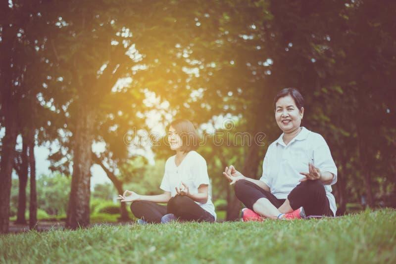 Verbinden Sie die asiatischen Frauen, die das Yoga morgens sitzend am Park üben, glücklich und am Lächeln, am Positivdenken, an g lizenzfreie stockfotos