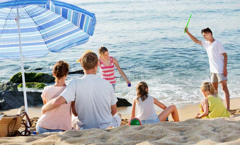 Verbinden Sie die Entspannung auf Strand während ihre Kinder, die aktive Spiele spielen stockbilder