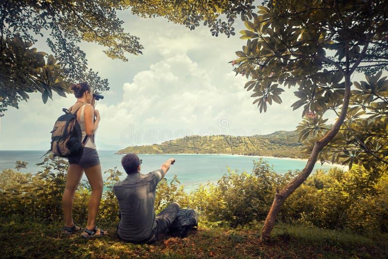 Verbinden Sie die Reisenden mit Rucksäcken aufpassend durch Ferngläser enj lizenzfreies stockfoto