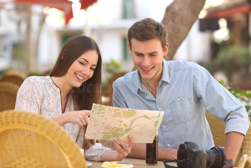 Verbinden Sie die Touristen, die einen Führer in einem Restaurant konsultieren lizenzfreies stockbild