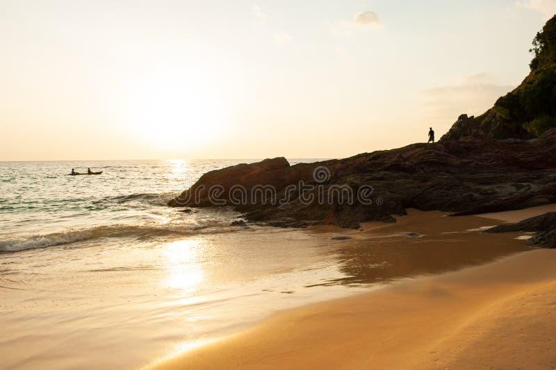 Verbinden Sie die Touristen, die im tropischen Meer am Abend Kayak fahren Schöner goldener Strand, Stein, Felsen und Wellen Fisch lizenzfreies stockbild