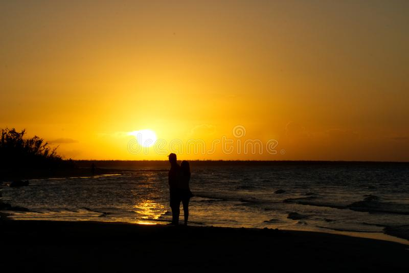 Verbinden Sie die Umfassung durch den Ozean bei Sonnenuntergang stockfoto