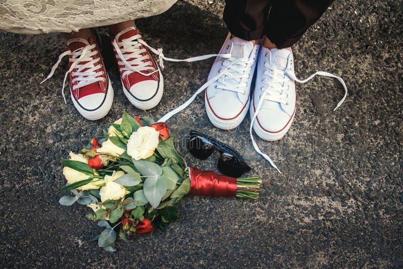 Verbinden Sie eben von den Hochzeiten mit lustigen gleichen Turnschuhen und Heiratsblumenstrauß, Sonnenbrille Blume und blaue Spi lizenzfreie stockfotografie