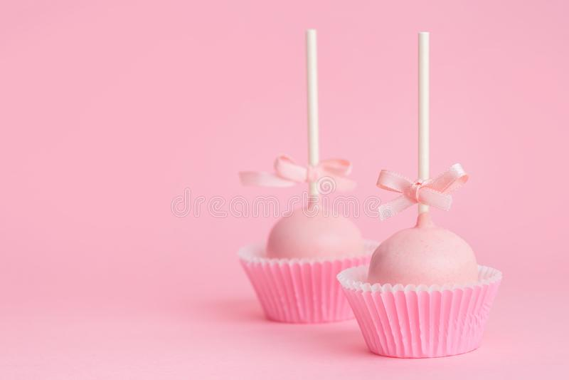 Verbinden Sie festlichen gefrierenden Kuchen knallt über rosa Hintergrund, Konzept von stockfotos