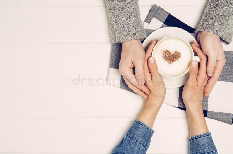 Verbinden Sie Händchenhalten mit Kaffee auf weißer Tabelle, Draufsicht stockfoto