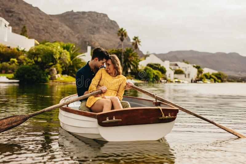 Verbinden Sie Haben des Spaßes, der in einem Boot auf einem Datum sitzt stockbilder