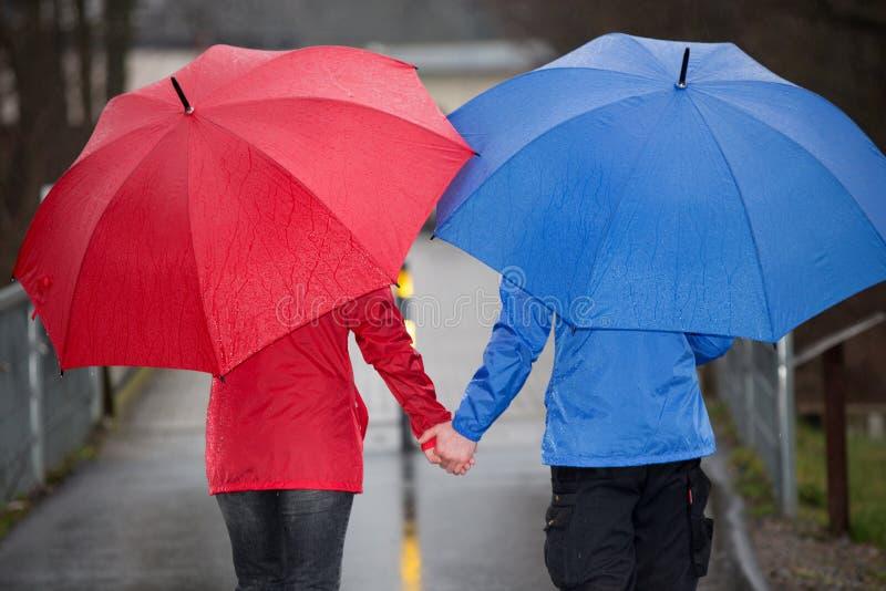 Verbinden Sie Hand in Hand Weg im Regen mit Regenschirm stockbilder