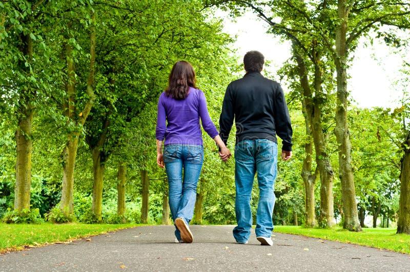 Verbinden Sie Holdinghände und das Gehen in einen Park lizenzfreies stockbild