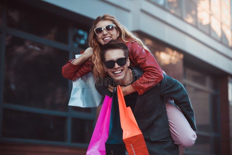 Verbinden Sie im Einkaufen zusammen Glückliches Paar, das zusammen kauft und Spaß hat Freund, der seine Freundin auf dem Doppelpo lizenzfreie stockbilder