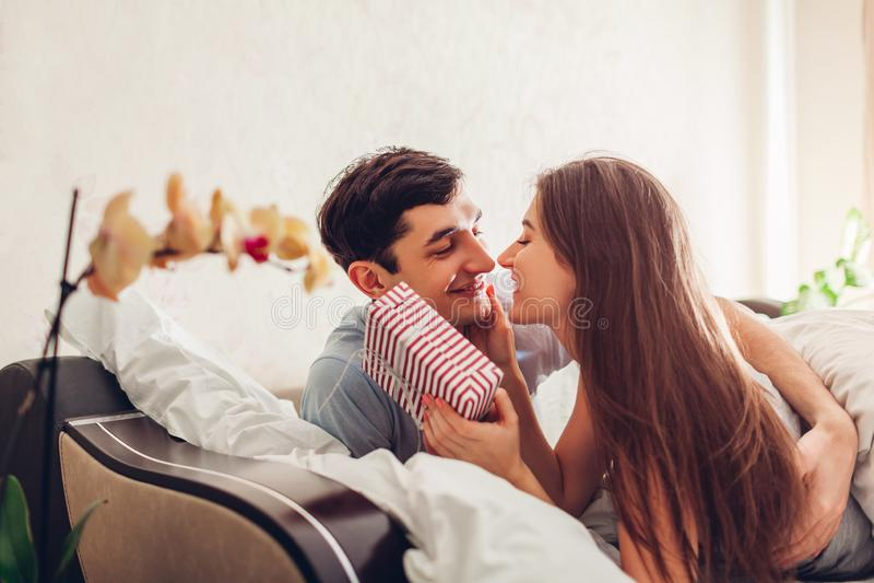Verbinden Sie in küssendem im Bett morgens liegen der Liebe Mann gibt seiner Freundin für Valentinsgrußtag Geschenkbox stockfoto