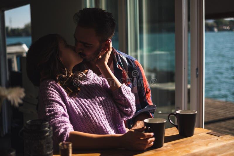 Verbinden Sie küssenden und trinkenden Kaffee durch den Fluss lizenzfreie stockbilder