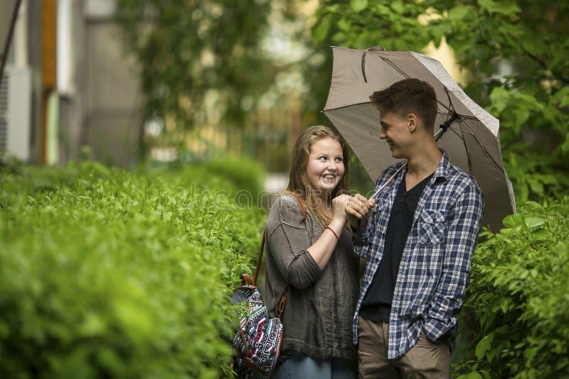 Verbinden Sie Kerl und Mädchen draußen unter einem Regenschirm im kleinen Regen stockbilder