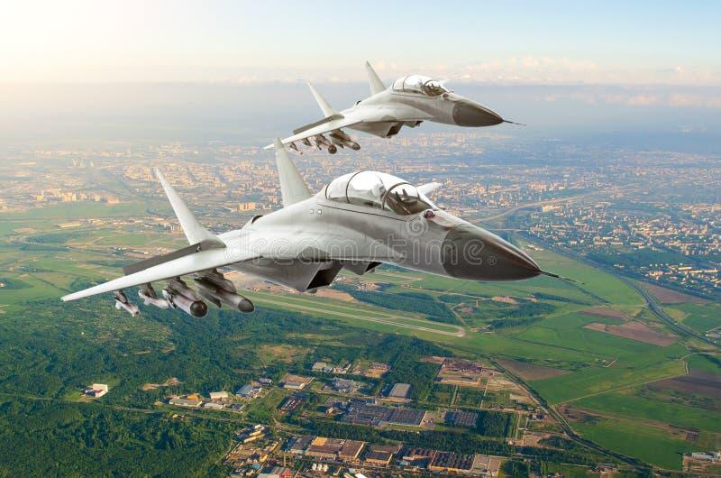 Verbinden Sie Militärdüsenjägerflugzeuge und über die Stadt und den Flughafen hoch fliegen stockfoto