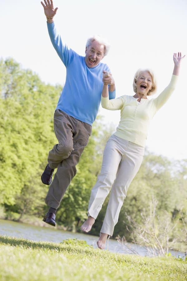 Verbinden Sie am Park draußen springen, indem Sie Seelächeln stockfotos