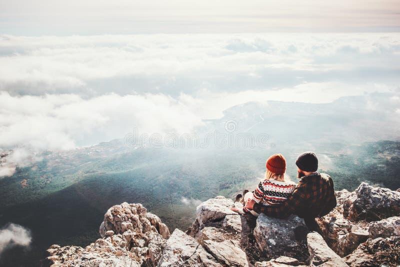 Verbinden Sie Reisende der Mann und Frau, die auf Klippe sitzen stockfoto