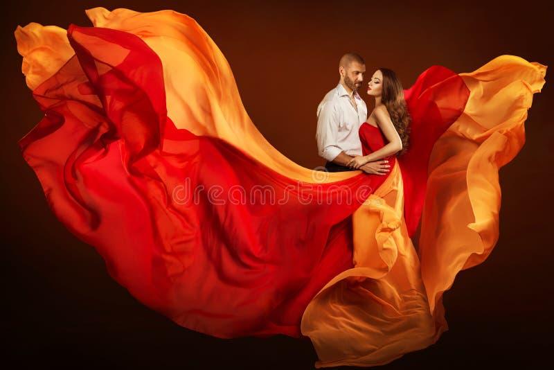 Verbinden Sie Schönheits-Porträt, Mann und Träumenfrau in wellenartig bewegendem Kleid als Flamme auf Wind stockbilder