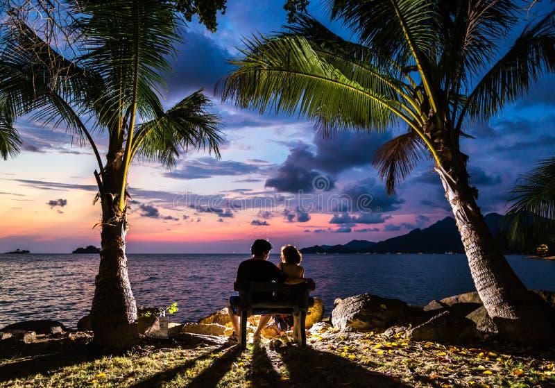 Verbinden Sie Umarmungsund aufpassende Sonne des Schattenbildes bei Sonnenuntergang auf dem bea lizenzfreie stockfotografie