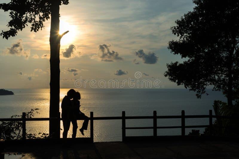 Verbinden Sie Umarmungsund aufpassende Sonne des Schattenbildes bei Sonnenuntergang auf dem bea stockfotos