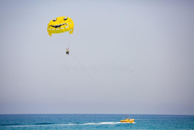 Verbinden Sie von den Touristen, die auf einen gelben Fallschirm mit lächelndem Gesicht auf ihm fliegen stockbild
