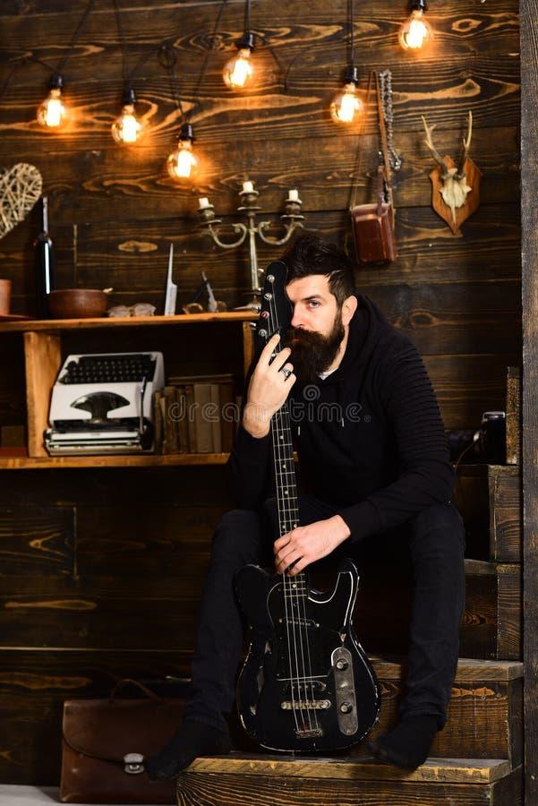 Verbinding door muziek Geniet van de mensen gebaarde musicus gelijk makend met basgitaar, houten achtergrond De kerel zit nadenke stock afbeeldingen